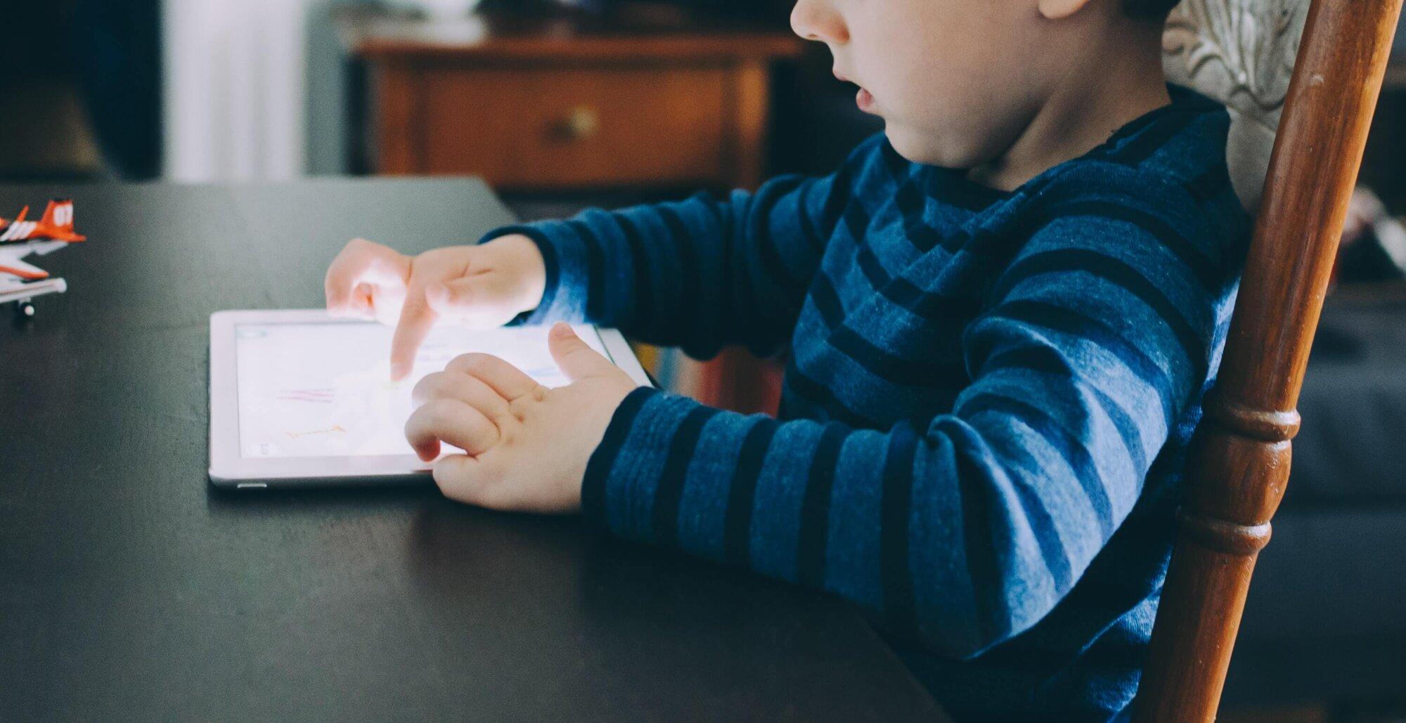 Ребенок сидит в планшете